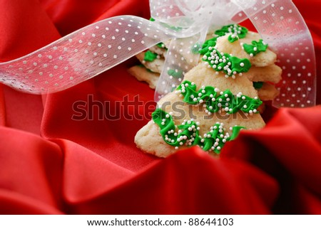 Freshly baked christmas tree cookies with ribbon on red satin.  Macro with shallow dof and copy space. - stock photo