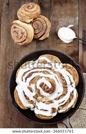 Freshly baked cinnamon buns in a cast iron skillet with extreme shallow depth of field. - stock photo