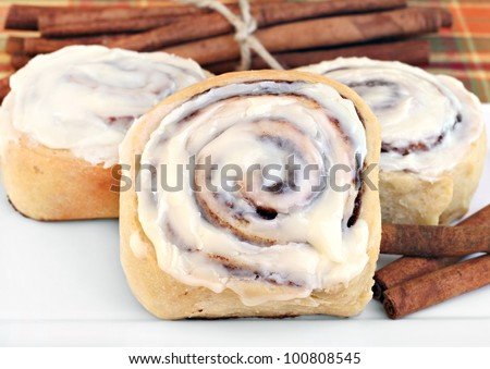 Freshly baked cinnamon buns with selective focus on standing front one. - stock photo
