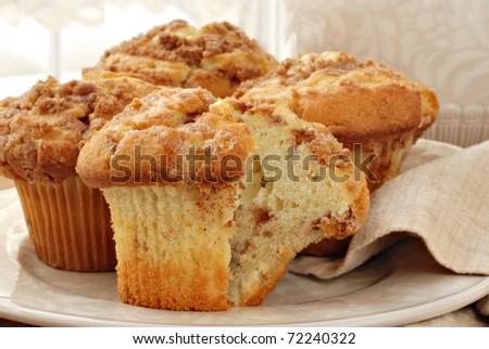 Freshly baked cinnamon muffins with sunlit window in background.  Closeup with shallow dof. - stock photo