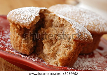 Freshly baked cinnamon spice muffin sprinkled with powdered sugar.  Macro with extremely shallow dof. - stock photo