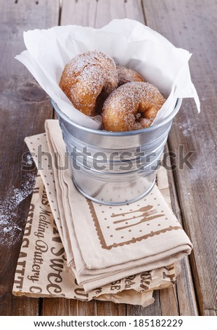 Freshly baked cinnamon sugared doughnuts in wrapping paper in the metal bucket on wooden background close up. Rustic still life - stock photo