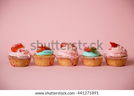 Freshly baked colorful cupcakes decorated with sprinkles and strawberries on pink background - stock photo