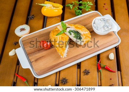 Freshly baked Cornish pasties on a wooden board - stock photo