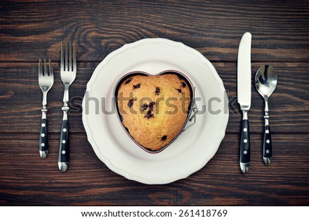 Freshly baked cranberry muffin in shape of heart. Top view. - stock photo