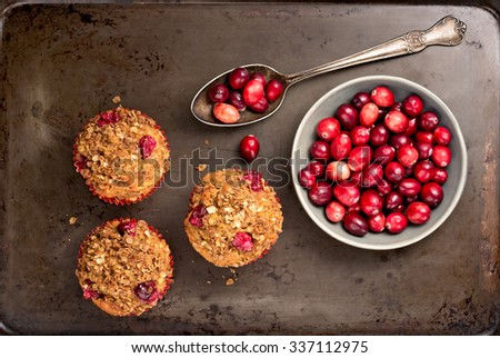 Freshly baked cranberry muffins on a rustic baking pan with cranberries.