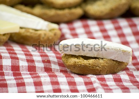 freshly baked crisp bread rolls with brie cheese over white and red cloth fabric - stock photo