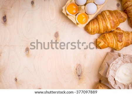 Freshly baked croissants and baguette with flour, eggs and egg yolks in a carton tray on the light wooden background. Baking/pastry background. Free space for text - stock photo