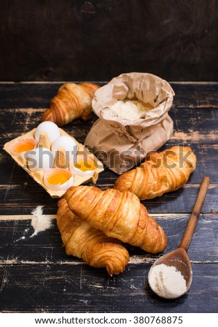 Freshly baked croissants with flour, rolling pin, spoon, eggs and egg yolks in a carton tray on the dark wooden background. Ingredients for baking - stock photo