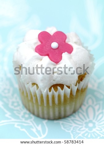 Freshly baked cup cakes with pink flowers and white frosting - stock photo