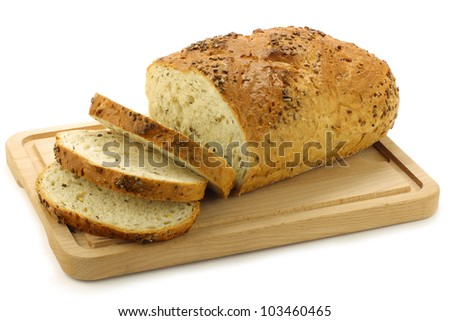 freshly baked cut loaf of cornbread on a wooden cutting board on a white background - stock photo