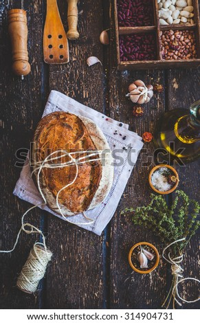 Freshly baked delicious crusty wholewheat seed bread with butter served on a rustic cloth in a country kitchen with a vintage kitchen accessories. Healthy food concept. - stock photo