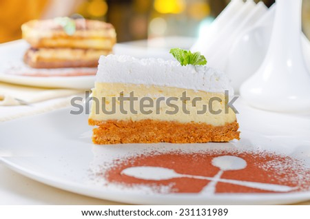 Freshly baked delicious slice of cheesecake with a biscuit base topped with cream presented on a plate with crossed spoon outline in chocolate powder