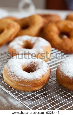 Freshly baked doughnuts sprinkled with icing sugar - stock photo