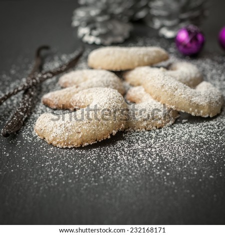 Freshly baked festive golden crescent cookies for Christmas and Advent sprinkled with icing sugar on a grey kitchen counter with Xmas decorations behind and shallow dof - stock photo