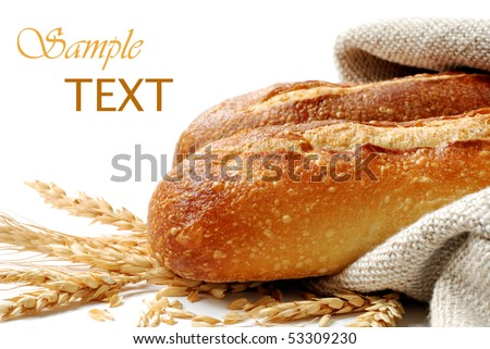 Freshly baked french bread with homespun fabric and wheat spikes on white background. - stock photo