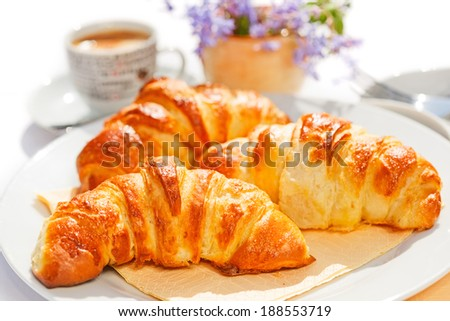 Freshly baked french butter croissants on plate - stock photo