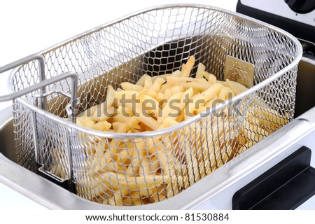 Freshly baked french fries in an electric frying pan basket - stock photo