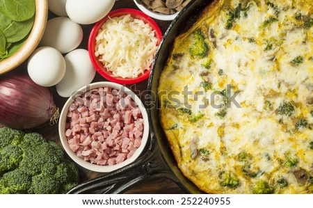 "freshly baked frittata baked in a cast iron skillet along with fresh vegetables and ingredients high angle view""broccoli and spinach frittata"" - stock photo"