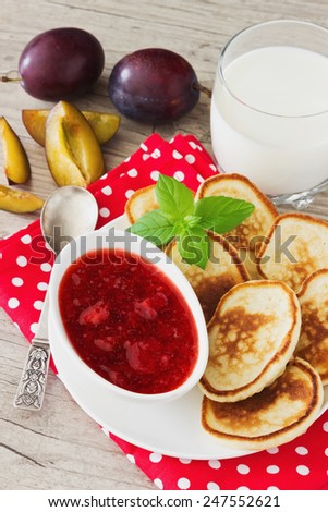 freshly baked fritters on a plate, strawberry jam, ripe plum, mint leaves and milk on the table. traditional european cuisine. - stock photo