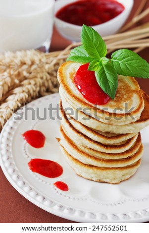 freshly baked fritters on a plate, strawberry jam, wheat stalks, leaves of mint and milk on the table. traditional european cuisine. selective focus. close-up - stock photo