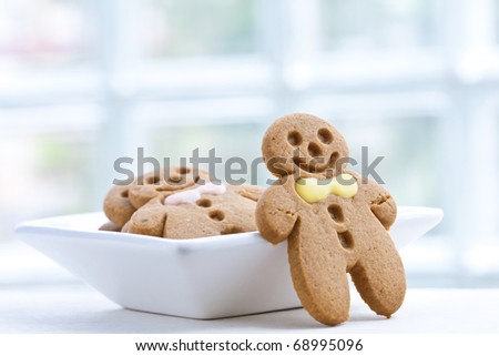 Freshly baked gingerbread biscuit in white plate - stock photo