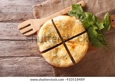 Freshly baked Greek pie with spinach on the table  horizontal view from above - stock photo