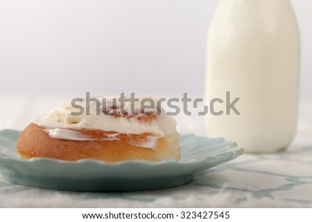 Freshly baked homemade cinnamon roll with cream cheese buttercream frosting and an antique bottle of milk close up shot - stock photo