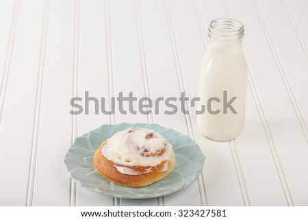 Freshly baked homemade cinnamon roll with cream cheese buttercream frosting and an antique bottle of milk - stock photo