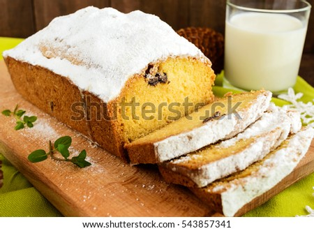 Freshly baked homemade  loaf cake, decorating the top with powdered sugar on a cutting board with a glass of milk.