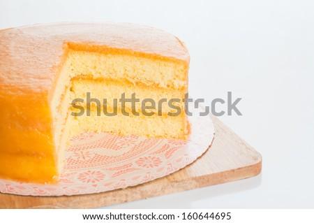 Freshly baked homemade orange cake on table. - stock photo