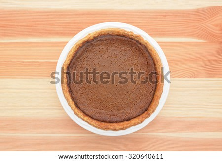 Freshly baked homemade pumpkin pie for Thanksgiving on a kitchen table - stock photo