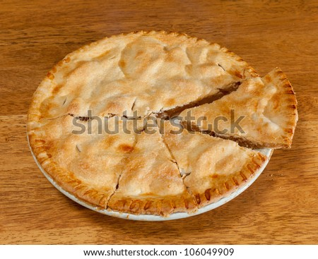 Freshly baked hot apple pie on wooden table - stock photo