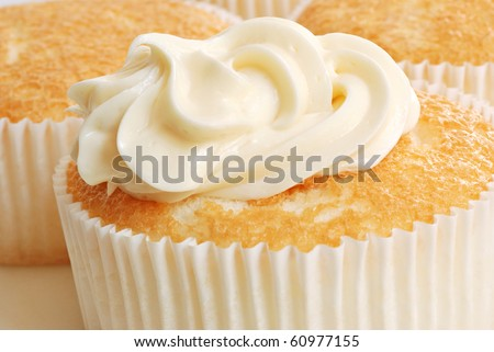 Freshly baked individual sized angel food cake with creamy swirl of vanilla frosting.  Macro with shallow dof. - stock photo