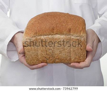 Freshly baked loaf of brown wholemeal bread being held by the baker who is wearing a white baker's coat. - stock photo