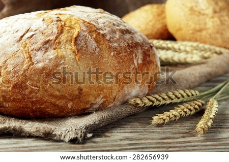 freshly baked loaf of homemade bread with wheat spikelets, lies on a wooden table. rustic style. closeup