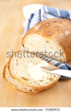 Freshly Baked Loaf of Yellow Potato Bread with Some Butter - stock photo
