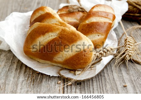 Freshly baked milky bread buns with ears of wheat placed over baking foil