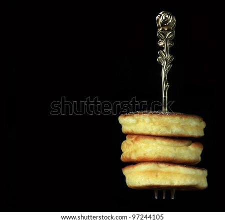 Freshly baked mini pancakes on fork against black background - stock photo