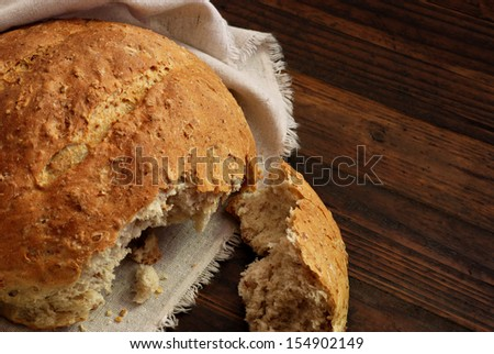 Freshly baked multi-grain bread with homespun fabric on rustic dark wood background.  Low key still life with directional natural lighting. - stock photo