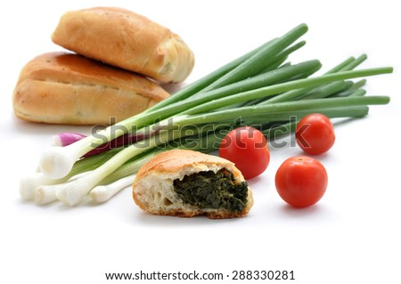Freshly baked onion turnovers on white background with green onion and tomato - stock photo