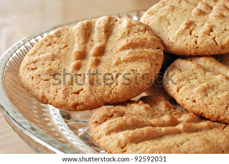 Freshly baked peanut butter cookies on crystal plate.  Macro with shallow dof. - stock photo