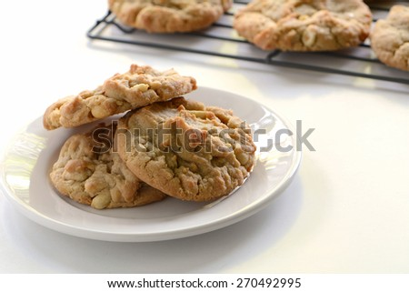 Freshly baked peanut butter cookies on white plate with other cookies on cooling rack in the background