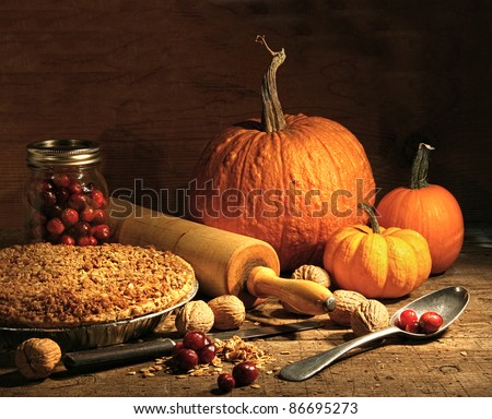 Freshly baked pie with pumpkin , nuts and cranberries on rustic table - stock photo