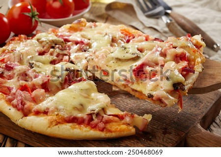 freshly baked pizza on wooden table - stock photo