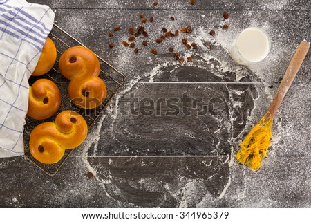 Freshly baked saffron buns on cooling rack partly under a cloth on the floury table with raisins, a glass of milk and a wooden fork with sticky yellow saffron dough.  - stock photo