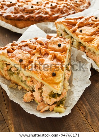 Freshly baked salmon pie wrapped in paper. Shallow dof. - stock photo