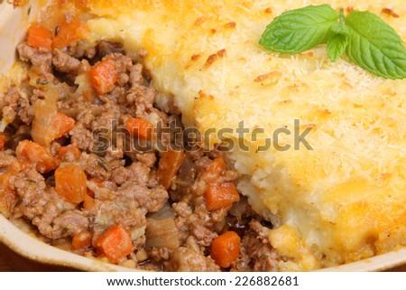 Freshly baked shepherds pie in casserole dish. - stock photo