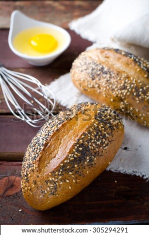 Freshly baked small breads with sesame and poppy seeds. Selective focus - stock photo
