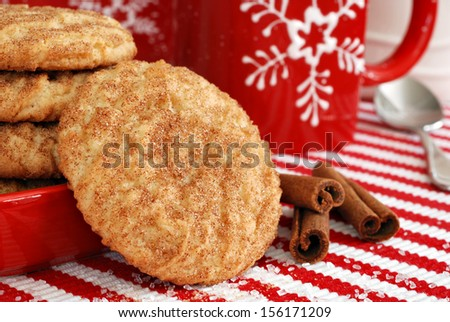 Freshly baked snickerdoodle cookies with cinnamon sticks and snowflake mug on festive holiday placemat. (sugar crystals scattered in foreground)  Closeup with shallow dof. - stock photo